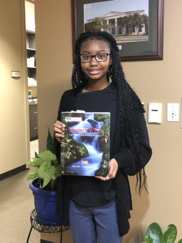 Mackenzie Hayes, Water Conservation Education Intern at the Athens-Clarke County Unified Government, poses with a copy of the Project WET Curriculum and Activity Guide 2.0