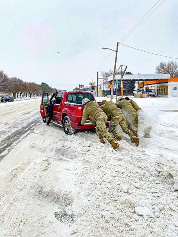 Texas Guardsmen assist a motorist stuck on snow and ice during extreme winter weather conditions in Abilene, Texas. Service members from the Texas Army, Air and State Guards worked in support of the Texas Department of Public Safety and Texas Division of Emergency Management transporting personal to safety, assisting stranded motorists, clearing roadways, manning warming centers, transporting critical infrastructure personnel to work, and delivering basic commodities like water, food, blankets and oxygen to